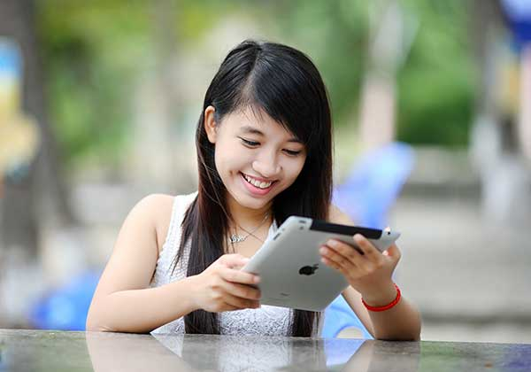 Image of a girl smiling at her Ipad