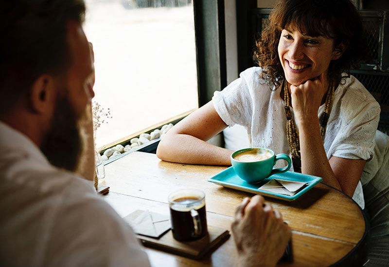 two people drinking coffee in a meeting